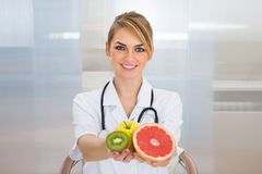 Female dietician holding fruits. Portrait Of Happy Female Dietician Holding Fruits stock photo