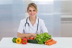 Female dietician with vegetables. Portrait Of Female Dietician With Vegetables On Desk royalty free stock photos