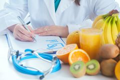 Female dietician writing a diet list. With fresh season fruit Royalty Free Stock Photo