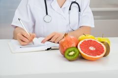 Female dietician writing prescription. Close-up Of Female Dietician Writing Prescription With Fruits On Desk royalty free stock photo