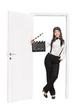 Female director holding a clapper and leaning on door Royalty Free Stock Images