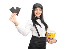 Female director holding popcorn and two tickets. Cheerful female movie director holding a box of popcorn and two tickets isolated on white background Stock Photo