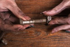 Female dirty hands screw nut bolt modern job Royalty Free Stock Photos