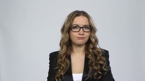 Female disappointed looks in camera and shrugs then waving his head no against grey background. At studio. Girl with wavy hair and glasses wearing a black stock footage