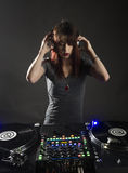 Female Disc Jockey at her Deck with Headphone Royalty Free Stock Images