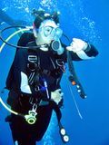 Female Diver. Watching the dive computer while doing a safety stop Royalty Free Stock Photography