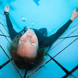 Female diver with eyes closed underwater in swimming pool Royalty Free Stock Image