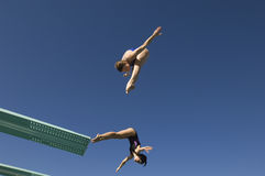 Female Divers Diving In Midair stock photos