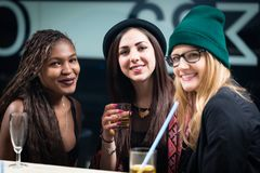 Female diverse friends enjoying drinks at party stock photos