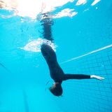 Female diving downwards in swimming pool Royalty Free Stock Image
