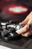 Female DJ adjusting turntable tonearm Royalty Free Stock Images