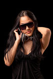 Female DJ in a black dress. A young asian girl in a black dress and sunglassses listening to music from dj style headphones Stock Photography