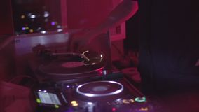 Female DJ choosing vinyl record to play music on a turntable in nightclub. Stock footage stock video footage