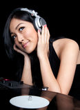 Female DJ in front of turntables. A female DJ listening to music on a pair of turntables Stock Photos