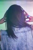 Female DJ listening music on headphone Stock Image