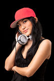 Female DJ listening to music. A young asian girl in a black dress and red hat listening to music from dj style headphones Royalty Free Stock Photography