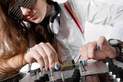 Female DJ playing music from vinyl. Young disc jockey girl crossfading tracks on professional mixing controller Royalty Free Stock Images