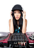 Female DJ posing for a photo. A young female Asian DJ posing in for a photo in front of a mixer and turntables Stock Photos