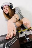 Female DJ scratching the record. Young attractive teenage girl playing music from turntable Royalty Free Stock Photo