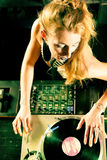 Female DJ at the turntable in Club. Female DJ at the turntable in a club, with mixer and old school record player Royalty Free Stock Image