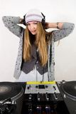 Female DJ at the turntables. Young attractive disc jockey girl in headphones Royalty Free Stock Photo