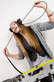 Female DJ at the turntables. Young girl having fun with her headphones cable at the mixing controller Stock Photo