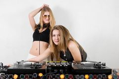 Female DJs at the turntables. Couple of pretty chicks playing music from a vinyl record Stock Photography
