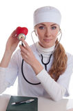 Female docotr examining red heart Royalty Free Stock Images