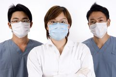 Female Doctor. A young asian female doctor is flanked by two men in scrubs Royalty Free Stock Photography