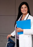 Female Doctor. Attractive female doctor standing holding a clipboard with a wheelchair Royalty Free Stock Photo