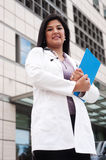 Female Doctor. Attractive female doctor standing outside and holding a clipboard Royalty Free Stock Photos
