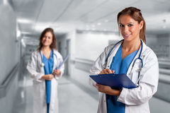 Female Doctor. Writing in a notepad inside an hospital. Another  is in the background Royalty Free Stock Image