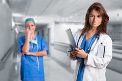 Female Doctor. Writing in a notepad inside an hospital. Another  is in the background Stock Photos