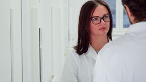 Female doctor agrees with her male colleague. Caucasian female doctor in glasses agreeing with her male colleague. Attractive brunette women in white coat stock images