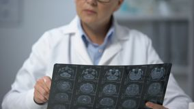 Female doctor analyzing brain x-ray and shaking head displeased with scan result