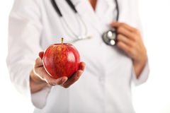 Female doctor with apple. Female doctor with red apple Royalty Free Stock Photography