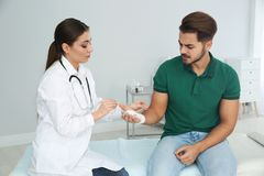 Female doctor applying bandage on young man`s hand in clinic. stock photography