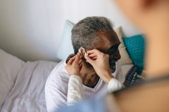 Female doctor applying hearing aid to senior man ear. High angle view of Asian female doctor applying hearing aid to senior African-american  man ear at stock photos