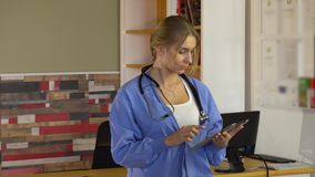 Female doctor appoints the date of admission of the patient using a digital tablet. Female doctor in blue lab coat with stethoscope on shes neck appoints the stock footage