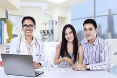 A female doctor with asian couple in doctor's office Stock Image