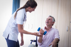 Female doctor assisting senior man in lifting dumbbell Stock Images