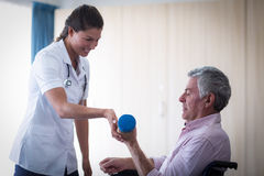Female doctor assisting senior man in lifting dumbbell Royalty Free Stock Image