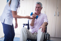 Female doctor assisting senior man in lifting dumbbell Stock Photo