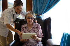 Female doctor assisting woman in using tablet at retirement home. Female doctor assisting women in using digital tablet at retirement home Stock Photography