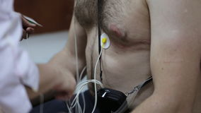 Female doctor attaching electrodes on patient`s chest to daily monitoring