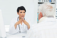 Female doctor attentively listening to senior patient Stock Photography