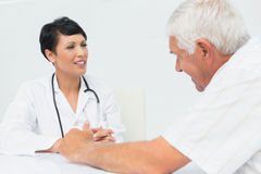 Female doctor attentively listening to senior patient Stock Images
