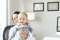 Female Doctor with Baby in Office. Thirties Woman Doctor with Baby in Office Stock Photos