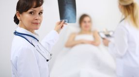 Female doctor at the background with patient. Physician at work stock images