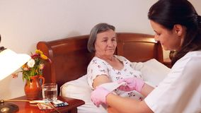 Female doctor bandages senior woman elbow at home stock footage